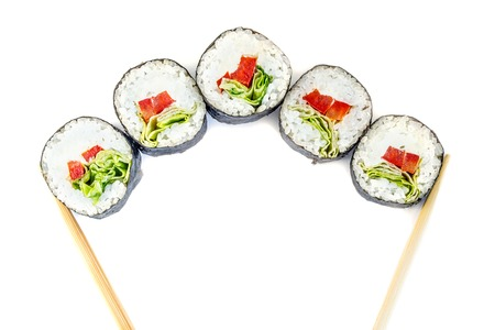 Sushi between chopsticks for sushi isolated on white background. Top view. Stock Photo