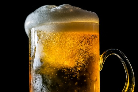 Beer overflowing large glass with foam and bubbles isolated on a black background Stock Photo