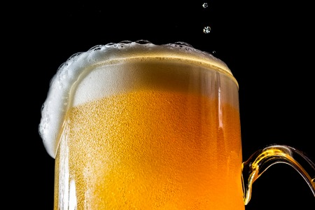 Stream of beer being pouring into a glass with beer and foam isolated on black background, closeup texture, splashing, splash Stockfoto