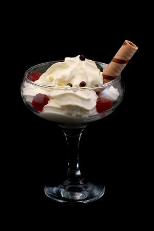 フランボワーズのジュレと黒の背景の美しいガラスにバニラ棒でチョコレート ボール アイス クリーム