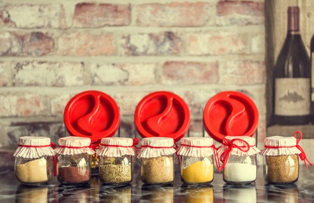 Spices in glass jars with beautiful covers, tied with red thread on dark table in the kitchen