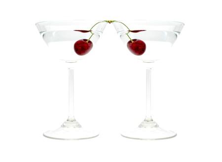 Glass of drink with cherry closeup isolated on white background
