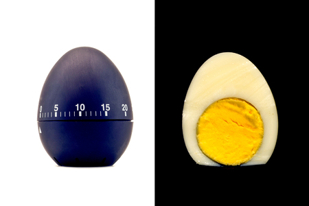 readiness: Timer as a black egg isolated on a white background and sliced boiled cooked egg refined with yolk on a black background