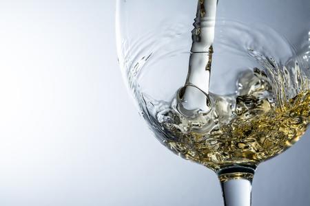 Stream of white wine pouring into a glass, white wine splash on grey background