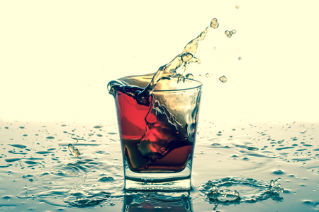 Splashing in glass with soda, ice cubes, white background