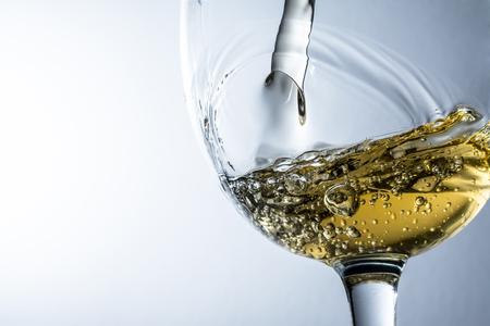 White wine splash on grey background, stream of white wine pouring into a glass. Stock Photo