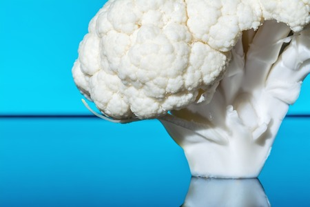 Fresh cauliflower with water drops close-up macro on a blue background Stock Photo