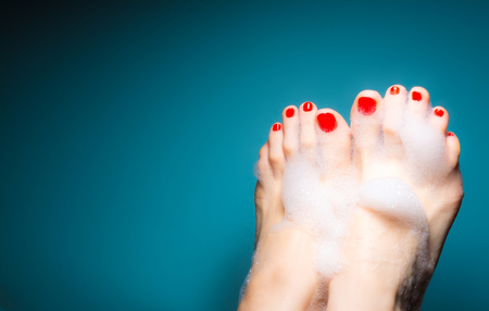 Feet of a young girl with red nails in a thick foam on a blue background