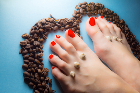 uñas pintadas: Feet of a young girl with red nails with drops of cream scrub and coffee beans around on a blue background