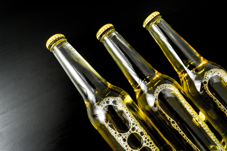 Beer in bottles with bubbles closeup on dark background wooden table
