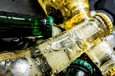 Beer in bottles with bubbles in ice cubes closeup on a dark background Stock Photo