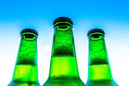 Beer in bottles with bubbles closeup on a blue sky background