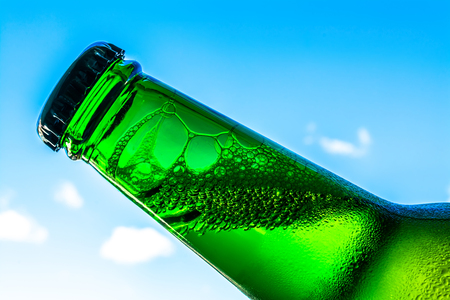 Beer in bottle with bubbles closeup on a blue sky background