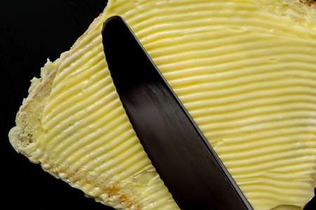 Butter with beautiful stains and a knife on a piece of bread close-up on a dark background