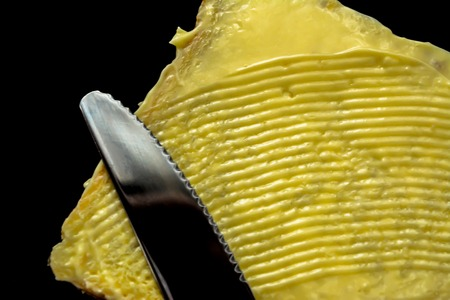 Butter with beautiful stains and a knife on a piece of bread close-up isolated on a black background