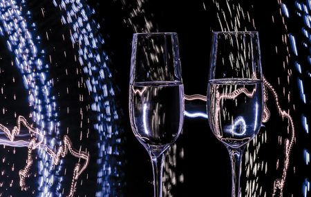 two: Two glasses of champagne wine on a background of abstract colored lights in motion