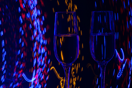 spot: Two glasses of champagne wine on a background of abstract colored lights in motion