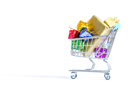 christmas gift: Shopping carts, trolley with boxes of colorful gifts isolated on white background Stock Photo
