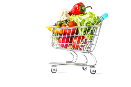 overcrowded: Shopping cart with fresh vegetables close-up isolated on white background
