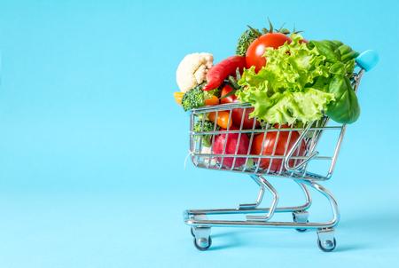 파란색 배경에 신선한 야채 근접와 쇼핑 카트