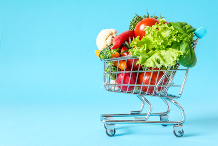 Shopping cart with fresh vegetables close-up on blue background Stockfoto