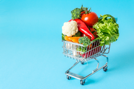 overcrowded: Shopping cart with fresh vegetables close-up on blue background Stock Photo