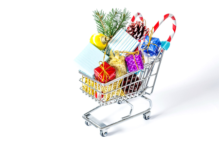 New Year's gifts in a shopping trolley close-up isolated on a white background. A shopping cart full of Christmas gifts isolated on white background.
