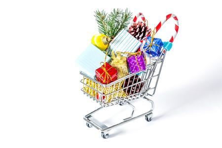 De giften van het nieuwjaar in een het winkelen karretjeclose-up op een witte achtergrond wordt geïsoleerd die. Een winkelwagentje vol kerstcadeaus geïsoleerd op een witte achtergrond. Stockfoto - 92345259
