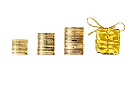 commercial event: Gift box in gold packing bandaged with a bow next to coins column close-up isolated on white background