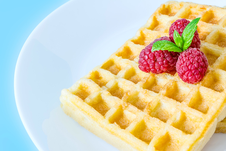 Sweet toast waffles with raspberries and a sprig of mint leaves on top on a white plate close-up macro on a blue background