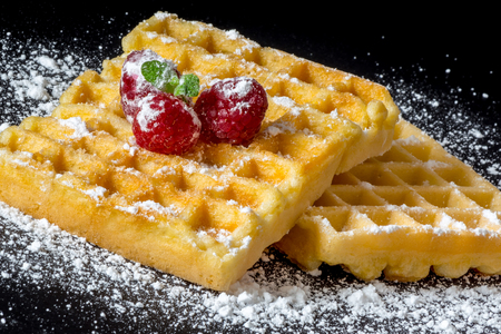 Sweet toast waffles with raspberries and a sprig of mint leaves on top and sugar powder close-up macro on a black background