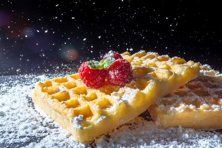 Zoete toast wafels met frambozen en een takje muntblaadjes op de top en zeven stromende suiker poeder in het zonlicht close-up macro op een zwarte achtergrond Stockfoto - 90672878