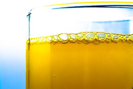 Bubbles of orange soda in a glass closeup macro textured background