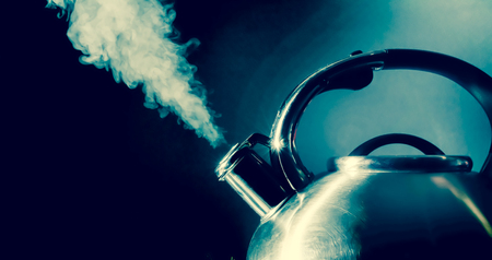 Kettle whistling, boiling kettle, steam, isolated on a black background Stockfoto