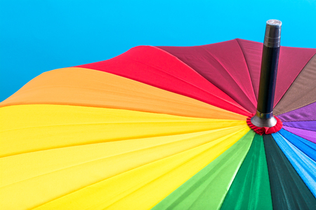 Multi-colored colorful umbrella with all colors of the rainbow on a blue background. Bright texture background. Stock Photo