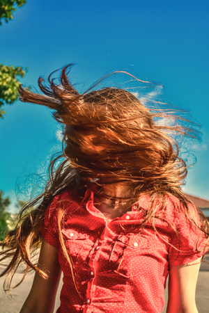 A young girl in the sunlight with long hair fluttering in the wind. A young girl with long fluttering hair shakes her head in the rays of the sun on the blue sky background. Vintage, grunge, old, retro style photo. Stock Photo