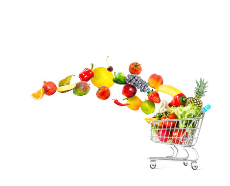 Fresh vegetables and fruits fly in a crowded shopping cart isolated on a white background Stock Photo