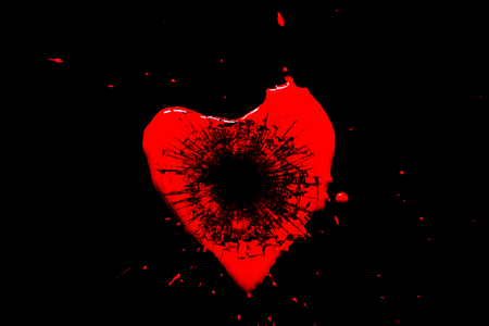 Red heart symbol broken into small splinters of glass from a shot from a pistol with a hole from a bullet isolated on a black background. Allegory of the unhappy love of a broken heart.