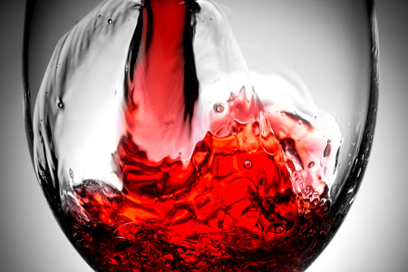 Red wine splash in the wineglass close-up macro texture background. Vintage old retro style view. Soft focus.