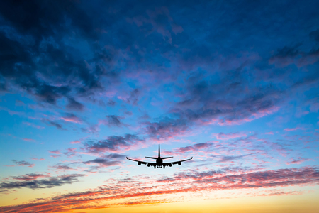 Colorful bright sunset with flying airplane silhouette Фото со стока
