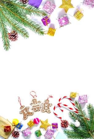 Branch of a Christmas tree with balls, fir cones, traditional candies and boxes with gifts isolated on a white background. Christmas and New Year background with free space for text.