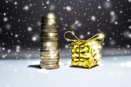 New Year's still-life with a stack of gold coins and a box with a gift on a dark background with falling snow 스톡 콘텐츠