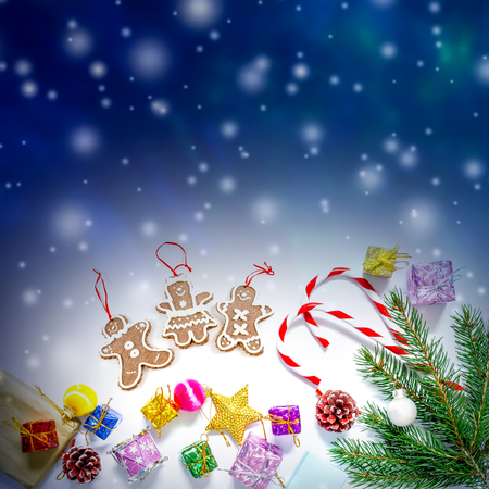 Beautiful Christmas and New Year`s background with Christmas tree branches, toys and sweets, falling snow and free space for text.