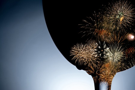Colorful fireworks against the black silhouette of a wine glass closeup. Fireworks inside the silhouette of a glass of wine.