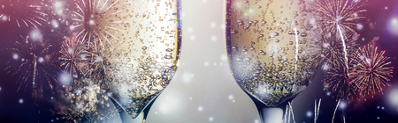 Colorful fireworks and two glasses of wine fizz champagne with bubbles close-up on the falling snow background. Stock Photo