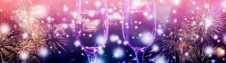 Colorful fireworks and two glasses of wine fizz champagne with bubbles close-up on the falling snow background. Banco de Imagens