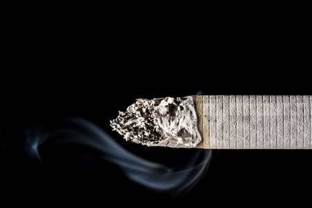 Burning smoldering cigarette close-up with beautiful smoke isolated on black background