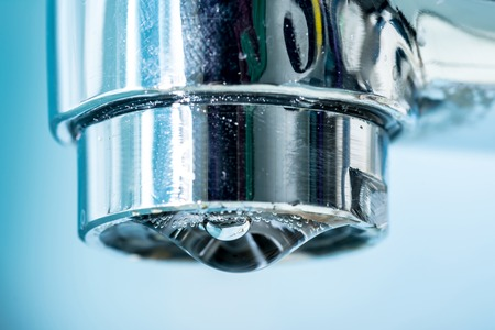 A drop of water hangs out of a modern chrome plated water tap faucet macro close up.