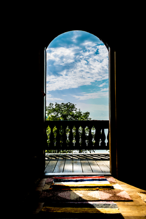 View of the forest landscape with a lake on a clear sunny day through the open door of a house with an ancient terrace. Stock Photo
