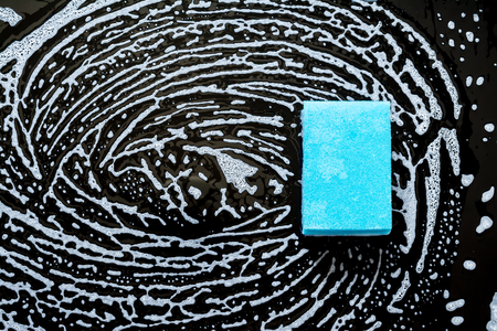 Blue sponge with beautiful divorces with foam close-up on a black glass background. Top view.